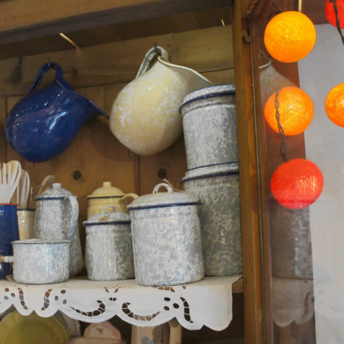 Είδη δώρων όπως εμαγιέ σκεύη στην παλιά παραδοσιακή ντουλάπα στο ισόγειο τής Στέρνας
